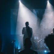Gitarrist der Lobpreisband rappt im Scheinwerferlicht und Nebel