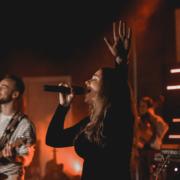 Sängerin der Lobpreisband mit erhobenen Händen in der Anbetung