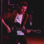 Gitarrist der Lobpreisband in der Anbetung kniend auf der Bühne